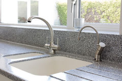 Kitchen mixer tap and sink. Modern kitchen granite worktop and ceramic sink with mixer tap stock photo