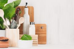 Kitchen modern decor - beige wooden utensils, brown cutting boards, green plant on soft light white wood background. Kitchen modern decor - beige wooden stock images