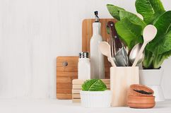 Kitchen modern decor - beige wooden utensils, brown cutting boards, green plant on soft light white wood background. Kitchen modern decor - beige wooden Stock Photos
