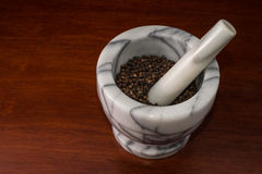 Kitchen mortar. Marble mortar with pepper inside on a wood table Stock Image