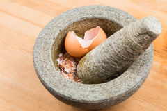 Kitchen mortar and pestle with crashed egg shell Stock Image