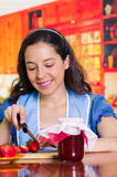 Kitchen is not easy, smiling woman preparing a famous recipe with strawberries Royalty Free Stock Image