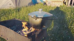 Kitchen outdoors.cooking at the stake. metal cauldron on the fire amid vegetation.close-up. Kitchen outdoors.cooking at the stake. metal cauldron on the fire stock footage
