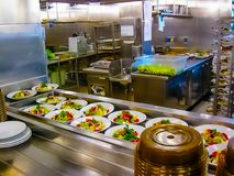 The kitchen with plates ready for serving dinner on a cruise ship Stock Photos