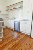 Kitchen With Polished Floorboards. A kitchen with white cupboards and pollished wood floor Royalty Free Stock Photo