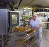 Kitchen Porter Pushes A Trolley Of Pastries. Female kitchen porter pushes a trolley of pastries stock image