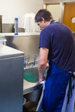 Kitchen porter standing behind sink Royalty Free Stock Photos