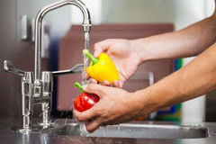 Kitchen porter washing pepper under running tap Royalty Free Stock Image