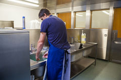 Kitchen porter washing up at sink Stock Photos