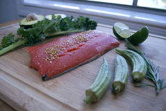At the kitchen. Preparing healthy food: alaskan red salmon with green vegetables. stock photography