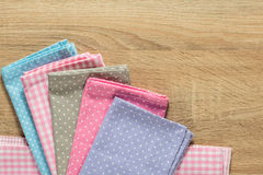 Kitchen rags in various colors. On wooden table Royalty Free Stock Photo