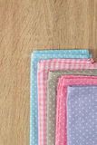 Kitchen rags in various colors. On wooden table Royalty Free Stock Photos
