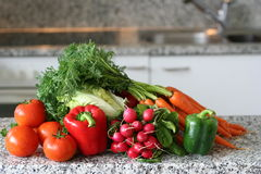 Kitchen with red vegetables. Kitchen composition with fresh vegetables on work table, with sink and cooking facilities in the background Stock Photos