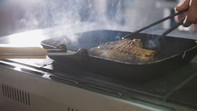 Kitchen of restaurant - chef is frying meat and vegetables in a pan stock images