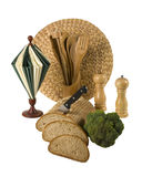 Kitchen retirement. Loaf of bread with knife, broccoli,pepper and salt, napkin paper, wooden cooking tools and rattan placement - all isolated over white Stock Photo