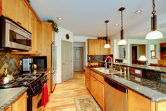 Kitchen room with brown cabinets, stainless steel, granite counter top. Stock Photo