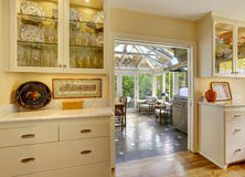 Kitchen room with exit to patio area in sunroom. Kitchen cabinets with glass doors and white granite tops stock photo