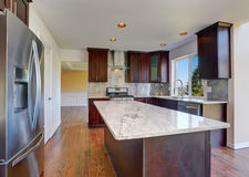Kitchen room interior with deep brown cabinets with granite counter top. Island and hardwood floor.Northwest, USA Royalty Free Stock Photos