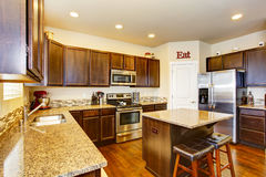 Kitchen room interior with deep brown cabinets, hardwood floor. And island. Northwest, USA Stock Images