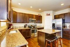 Kitchen room interior with deep brown cabinets, hardwood floor Stock Images