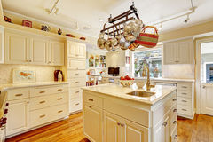 Kitchen room with island and hanging pot rack Royalty Free Stock Photo
