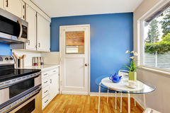 Kitchen room with white cabinets, blue walls and glass able Stock Photo