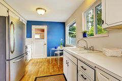 Kitchen room with white cabinets, blue walls and glass able Royalty Free Stock Photography