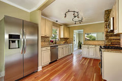 Kitchen room with white cabinets, stainless steel and hardwood floor Stock Images