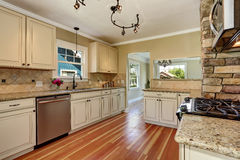 Kitchen room with white cabinets, stainless steel and hardwood floor Royalty Free Stock Photo