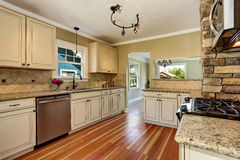 Kitchen room with white cabinets, stainless steel and hardwood floor Stock Photos