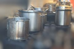In the Kitchen. A row of pots stands ready for use in a food tent at a regional festival Royalty Free Stock Image