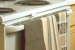 Kitchen's Stove Top/Oven & Dish Towels. Three patterns of dish towels hang off an oven's handle.  Electric burners are in the upper portion of the image. Light Stock Image