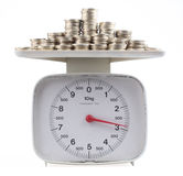 Kitchen scale. Isolated kitchen scale with pile of coins with clipping path Stock Photo