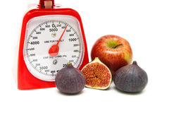 Kitchen scale, fig and apple on a white background Stock Images