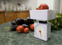 Kitchen scale and vegetables Stock Image