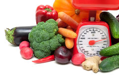 Kitchen scale and vegetables on a white background Royalty Free Stock Images