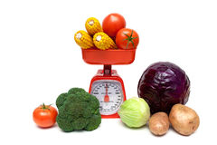 Kitchen scales and fresh vegetables isolated on white background Stock Photography