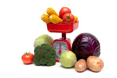 Kitchen scales and fresh vegetables isolated on white background Stock Photo