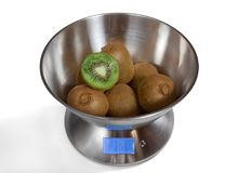 Kitchen Scales with Kiwis. Modern electronic metal kitchen weighing scales with kiwi fruits royalty free stock photo