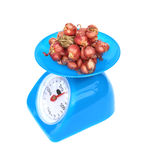 Kitchen scales and onions Royalty Free Stock Photos