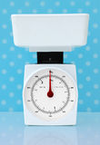 Kitchen scales weight loss diet concept. White weighing scales on blue polka dotted background Royalty Free Stock Image