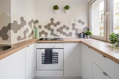 Kitchen in scandinavian style. With white cabinets, wooden countertop and hexagonal wall tiles royalty free stock images
