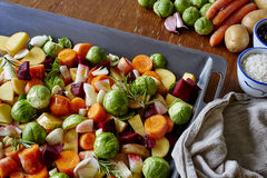Kitchen scene baking tray filled with organic vegetables Stock Photos