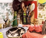 In the kitchen. Woman in rubber gloves. Scene in the kitchen depicting a sink, faucets, running water, utensils, washing dish chemicals also a woman washing a Stock Images