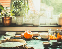 Kitchen scene with preparation of traditional festive pumpkin pie cooking on table at window Royalty Free Stock Photos