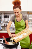 Kitchen scene - woman putting onion in the pan Stock Images