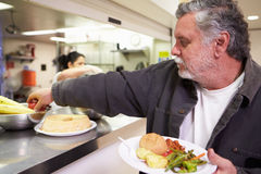 Kitchen Serving Food In Homeless Shelter Stock Images