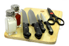 Kitchen set. Different sizes kitchen knifes, scissors, salt and pepper shakers over wooden cutting board Stock Photography