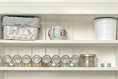 Kitchen shelf with jars. Kitchen interior with a fragment of a white shelf with a basket, sugar bowl and jars of ingredients stock images