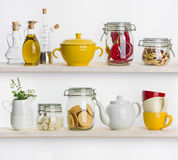 Kitchen shelves with various food ingredients and utensils on white. Kitchen shelves with various food ingredients and utensils isolated on white background Royalty Free Stock Photography